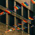 Rainbow pride flags on a string hanging between brick buildings